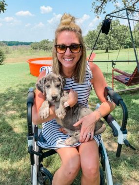Kendall sits outside on her walker and holds her Great Dane puppy, Hank. / Friedreich's Ataxia News